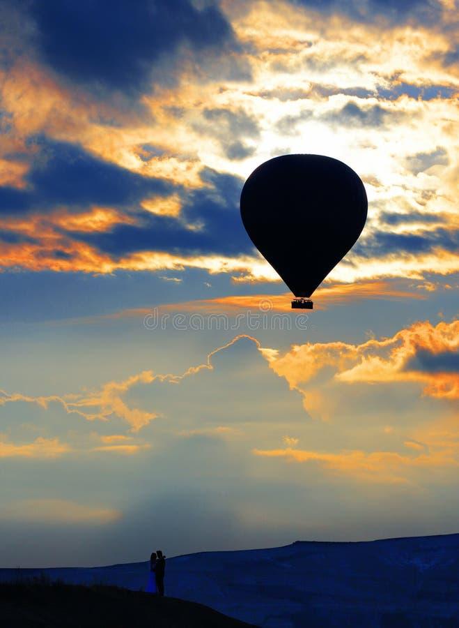 一个爱恋的夫妇和气球的剪影反对早晨天空与火红的云彩 免版税图库摄影