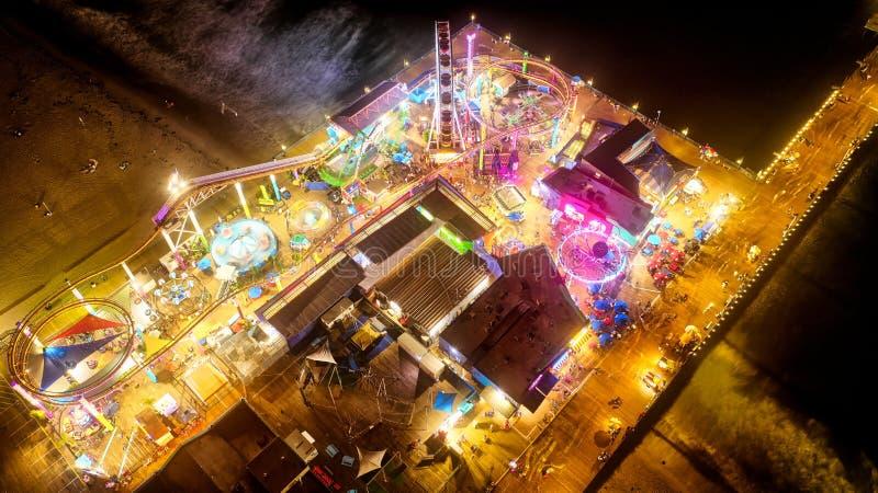一个狂欢节的空中射击在一个吸引力公园的在海滩附近在晚上 免版税库存照片