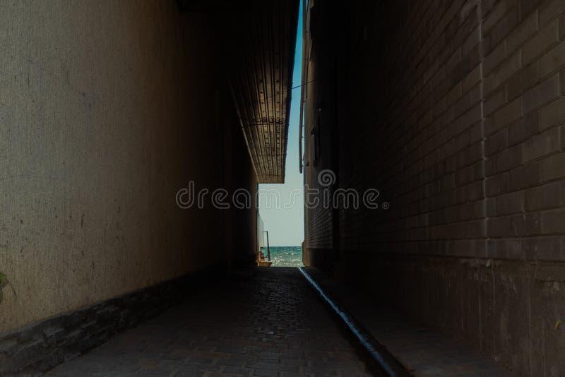 一个狭窄的段落向在房子之间的海 光在最后隧道的 免版税图库摄影
