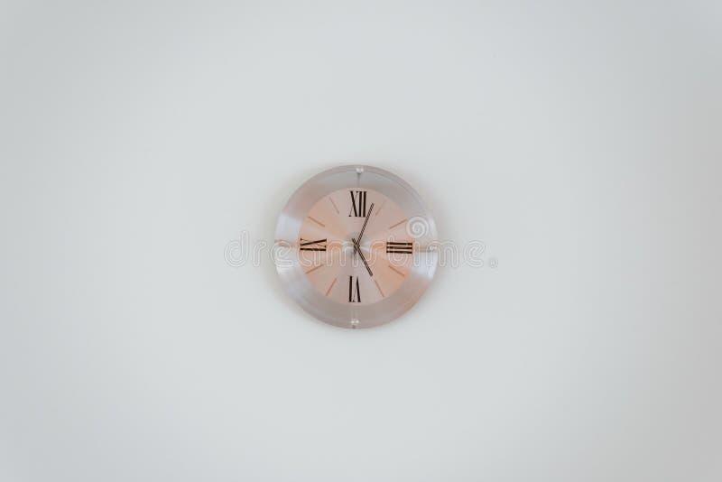 一个玫瑰色金壁钟的宽射击在白色墙壁上的 库存照片