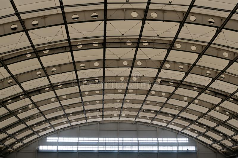 一个现代大厦的半球形的屋顶 在飞机棚、体育或者工厂厂房的半圆天花板 复制空间 库存照片
