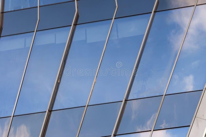 一个现代玻璃窗大厦的特写镜头与反射在它的天空蔚蓝和云彩的 免版税库存照片