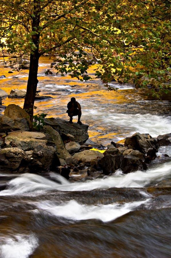 一个现出轮廓的人在山河观看潮流 免版税图库摄影