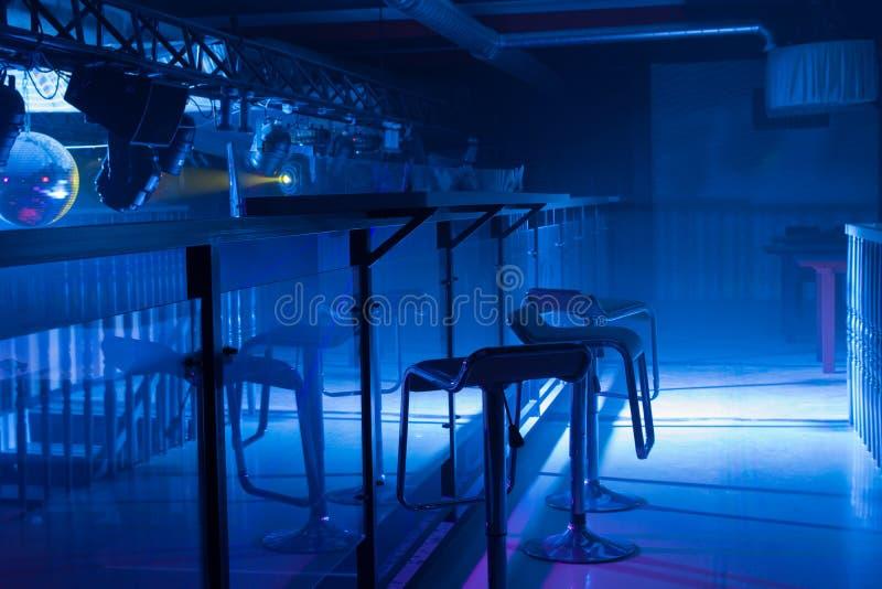 一个现代酒吧的内部与喜怒无常的蓝色照明设备的 库存照片