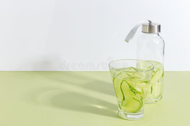 一个玻璃杯子和一个瓶在浅绿色的背景的黄瓜水 Minimalistic创造性的概念 复制空间 免版税库存图片