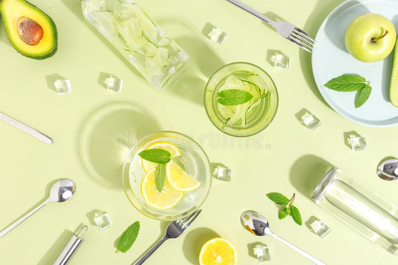 一个玻璃烧杯、一个瓶黄瓜水,果子和利器在浅绿色的背景 Minimalistic创造性的概念 复制 免版税库存照片