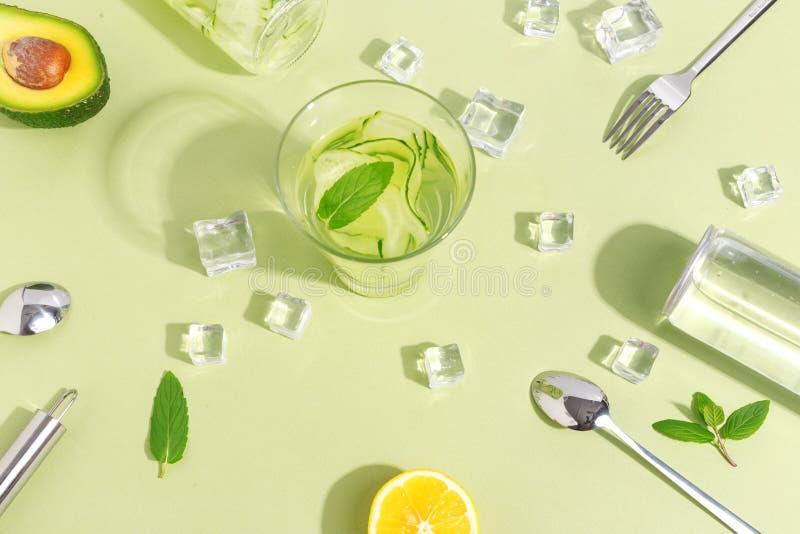 一个玻璃烧杯、一个瓶黄瓜水,果子和利器在浅绿色的背景 Minimalistic创造性的概念 复制 免版税库存图片