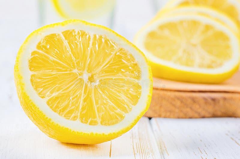 一个玻璃烧杯和一个水罐在柠檬围拢的白色木背景的冷的柠檬水 库存照片