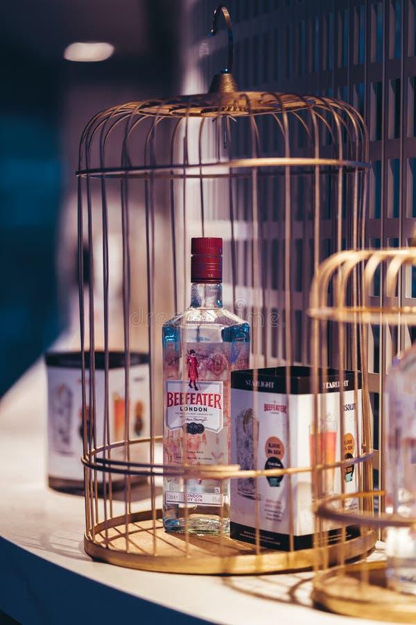 一个玻璃瓶在一只笼子的英王卫士杜松子酒在MS诗丽雅号小夜曲上的酒吧书桌 库存照片