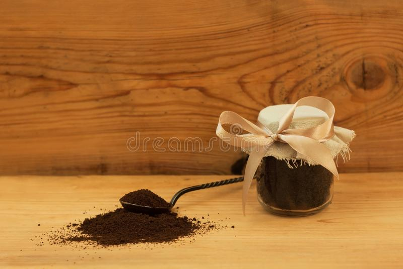 一个玻璃瓶子碾碎的咖啡,身体洗刷,混杂的糖,油,精华 剥皮的,温泉关心,拷贝空间自创化妆用品 免版税图库摄影