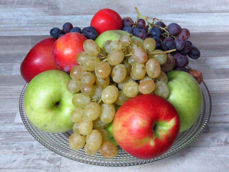 一个玻璃碗在白色洗涤山毛榉的木材土气神色背景的秋天果子 秋天果子收获苹果,葡萄,李子 免版税库存图片