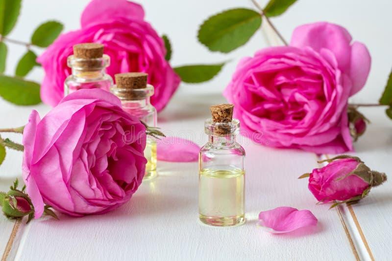 一个瓶与新鲜的玫瑰色花的精油 免版税图库摄影