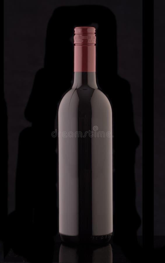 一个瓶在黑背景的红色精华酒 免版税库存图片