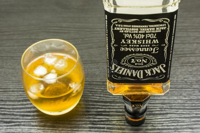 一个瓶威士忌酒忍耐了他的腿 并且一杯酒精 免版税库存图片