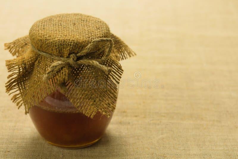 一个瓶子在桌上的蜂蜜 健康有机蜂蜜 免版税库存图片