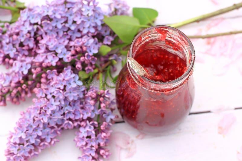 一个瓶子在轻的土气背景在庭院里,选择聚焦的新山莓果酱 免版税库存照片