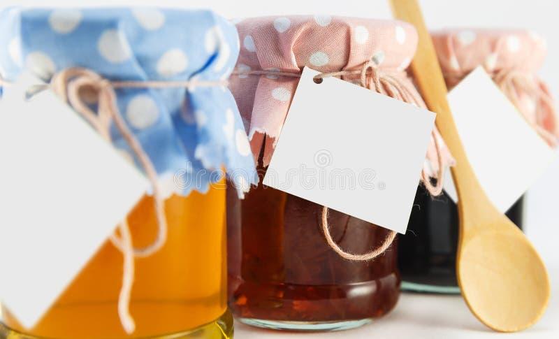 一个瓶子用蜂蜜,桑树和花在白色背景阻塞 库存图片