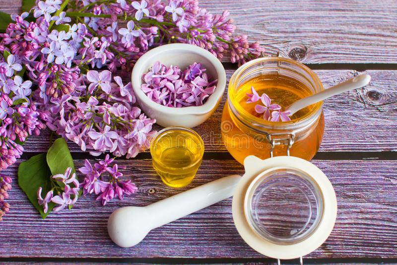 一个瓶子芬芳花蜂蜜 蜂蜜被保存的和淡紫色花 图库摄影