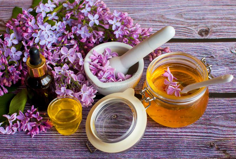 一个瓶子芬芳花蜂蜜 蜂蜜被保存的和淡紫色花 免版税库存图片