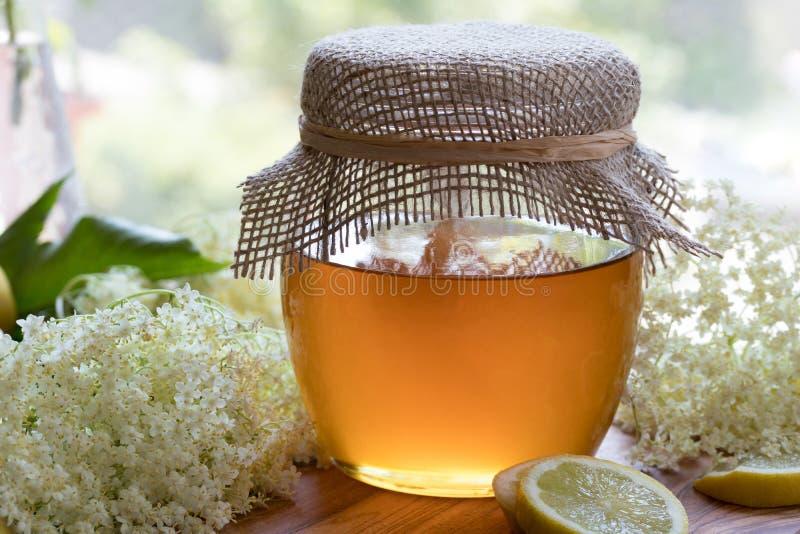 一个瓶子蜂蜜和长辈开花,准备做糖浆 库存照片