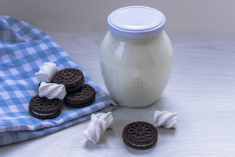 一个瓶子酸性稀奶油和曲奇饼在桌上 免版税库存照片