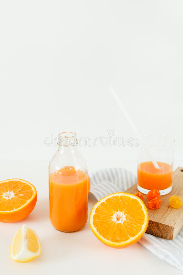一个瓶橙色新鲜在一张白色桌上,在一杯新鲜和桔子旁边用柠檬 免版税库存照片