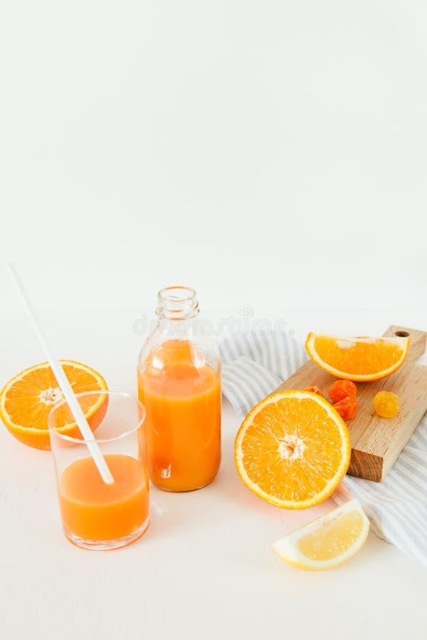 一个瓶橙色新鲜在一张白色桌上,在一杯新鲜和桔子旁边用柠檬 免版税库存图片