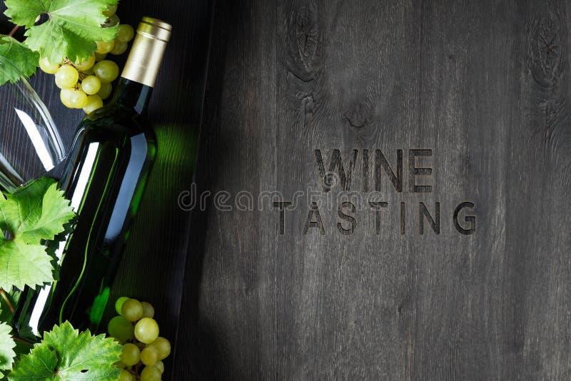 一个瓶白酒,一杯酒,一束葡萄在桌上的 r 库存图片