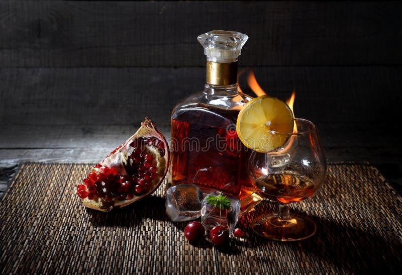 一个瓶科涅克白兰地、威士忌酒与取火镜和果子在木背景 免版税库存照片