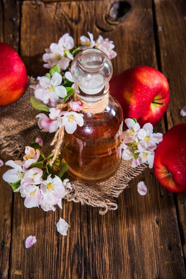 一个瓶苹果汁醋(萍果汁),新鲜的苹果和苹果树花在木背景 免版税库存照片