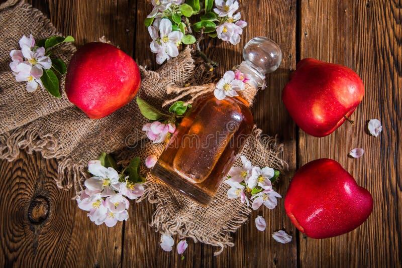一个瓶苹果汁醋(萍果汁),新鲜的苹果和苹果树花在木背景 免版税库存图片