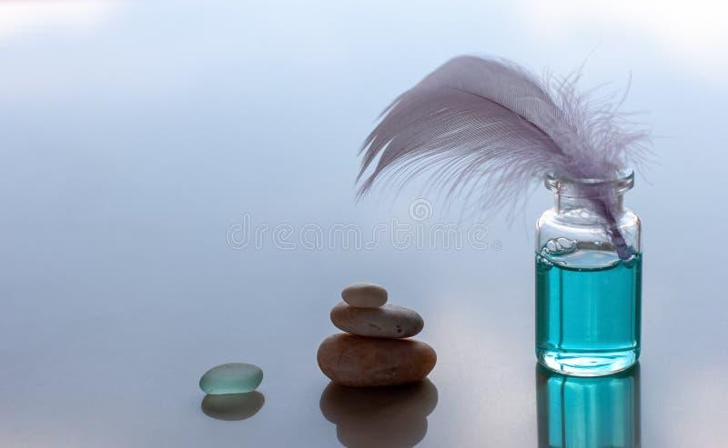 一个瓶蓝色有气味的油和黏附的鸟羽毛 图库摄影
