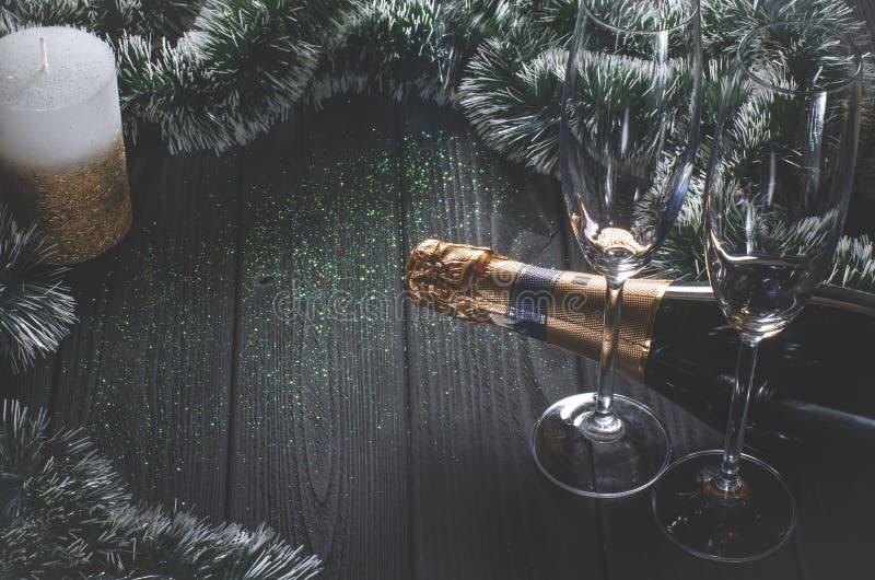 一个瓶香槟和两块玻璃在圣诞装饰和白金子围拢的一张深灰木桌上站立 免版税库存图片