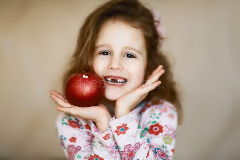 一个甜矮小的卷曲无牙的女孩微笑和举行在她的手上一个红色苹果,掉了乳齿一个愉快的孩子的画象 免版税图库摄影