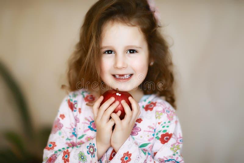 一个甜矮小的卷曲无牙的女孩微笑和举行她的棕榈的掉了乳齿的一个红色苹果 库存图片