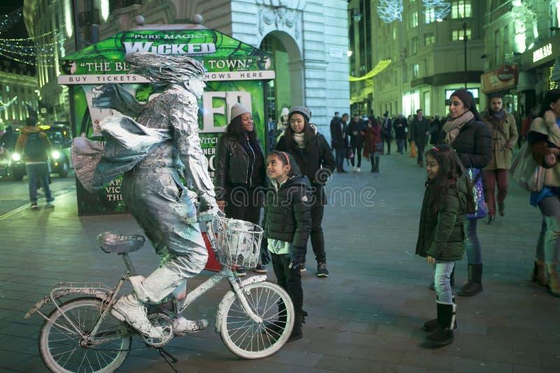 一个生存图是银色油漆的一个人在卡迪里的一辆自行车在伦敦在黄昏 免版税库存图片