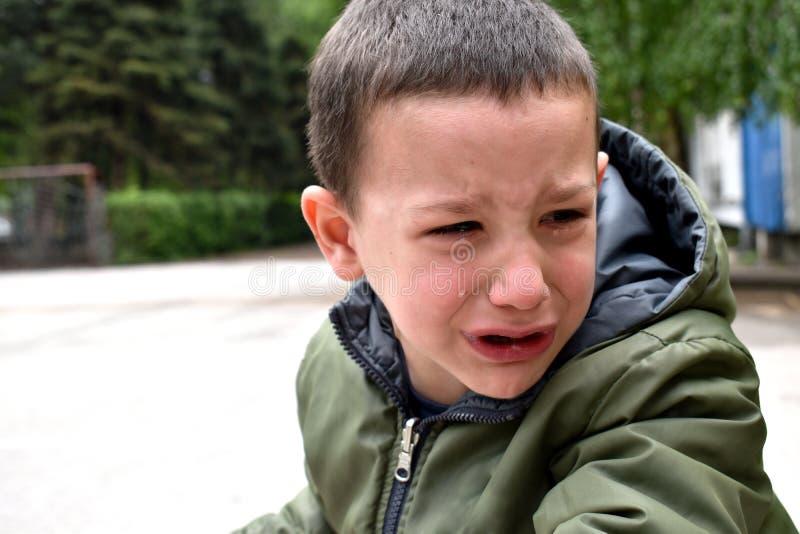 一个生气男孩,有面孔的哭泣由于与学会的困难骑自行车 免版税库存图片