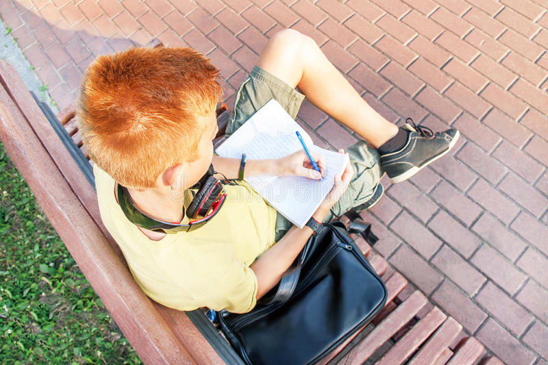 一个用左手的红头发人青少年的男孩的大角度画象 库存图片