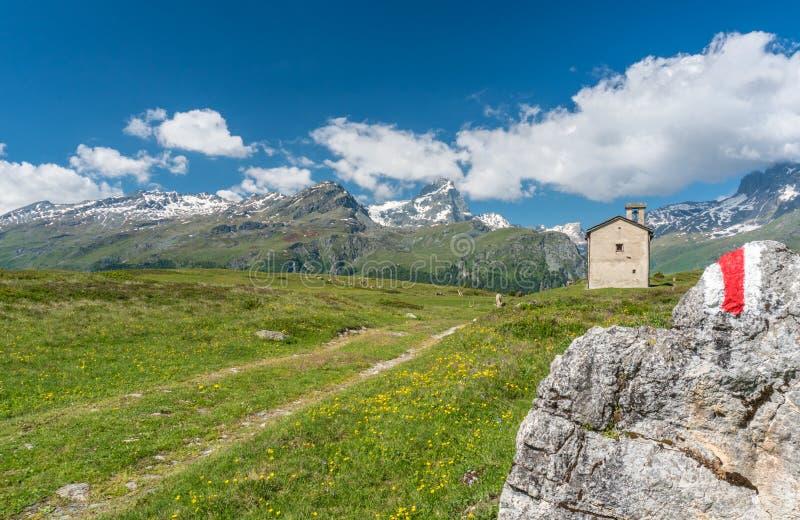 一个田园诗山风景的山教会夏令时在有积雪覆盖的峰顶的阿尔卑斯在背景和hiki中 库存照片