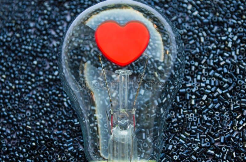 一个电电灯泡的红色心脏 免版税库存照片