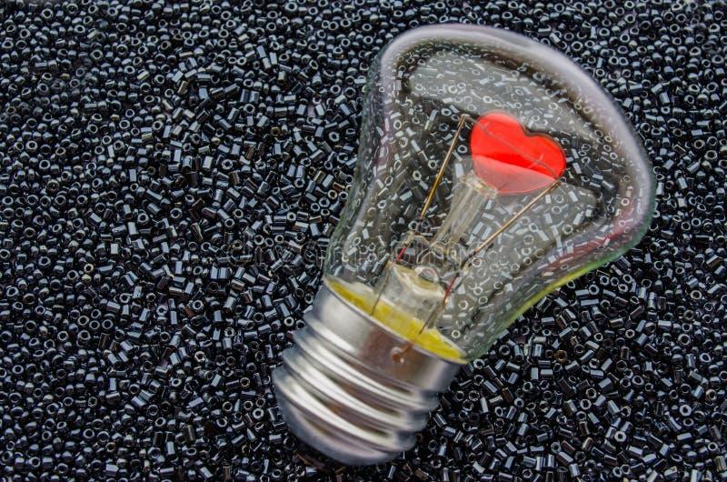 一个电电灯泡的红色心脏 免版税库存图片