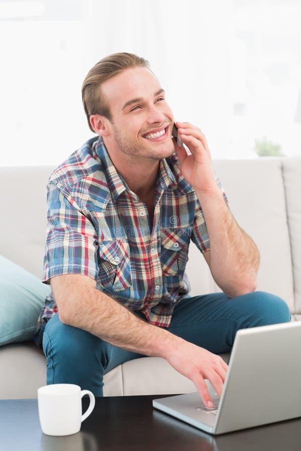 一个电话的微笑的人有膝上型计算机的在家 库存照片