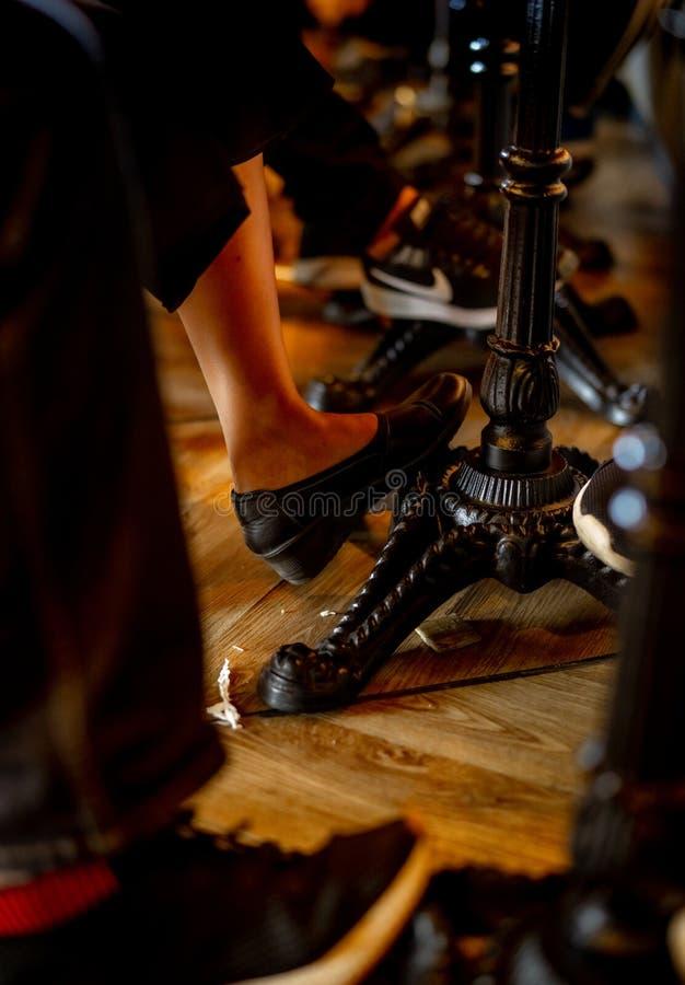 一个男人和一名妇女的特写镜头腿在桌下在咖啡馆 葡萄酒样式桌在餐馆 人们变冷  免版税图库摄影