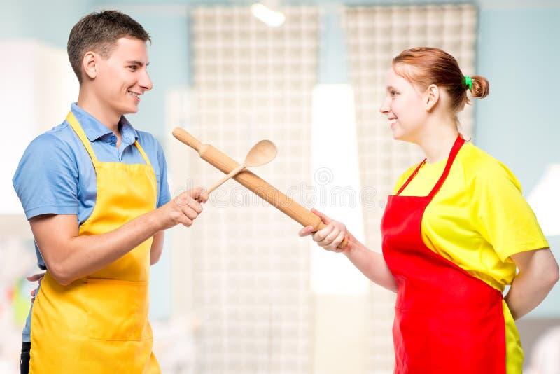 一个男人和一名妇女的画象一条围裙的与厨房用具战斗 免版税库存照片