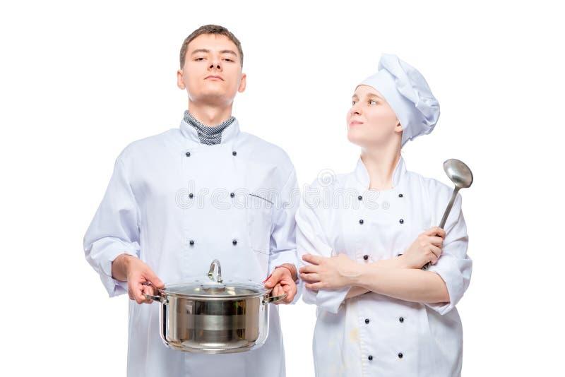 一个男人和一名妇女的画象摆在与一个平底锅的厨师衣服的在白色 免版税库存照片