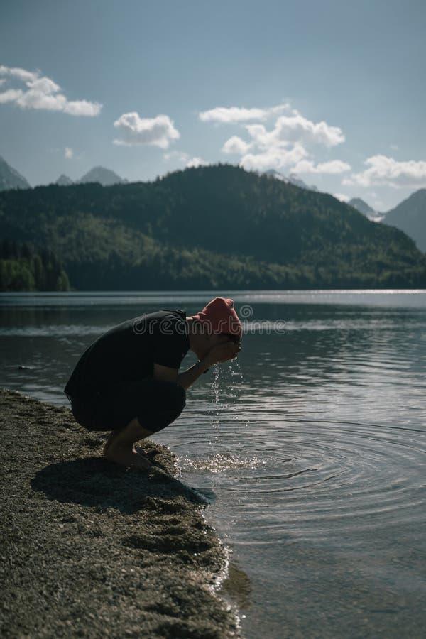 一个男人把手洗在森林湖的岸边 库存照片