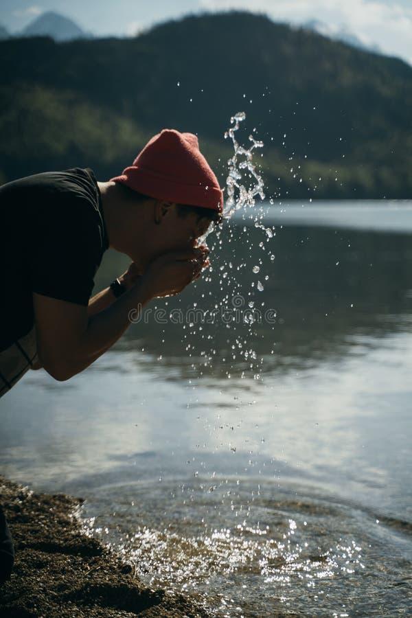 一个男人把手洗在森林湖的岸边 免版税库存照片
