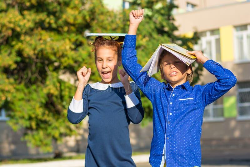 一个男孩和一个女孩有书的在他们的头是愉快的关于新的学年 免版税库存图片