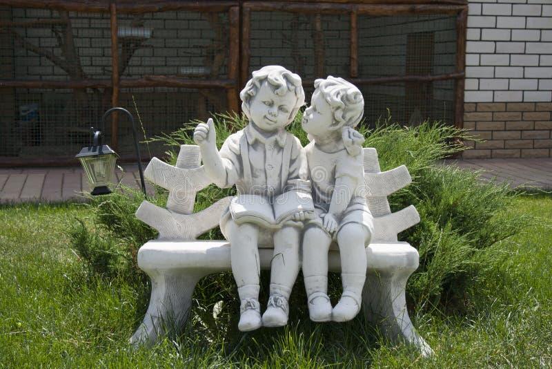 一个男孩和一个女孩的小雕象长凳的 免版税库存照片