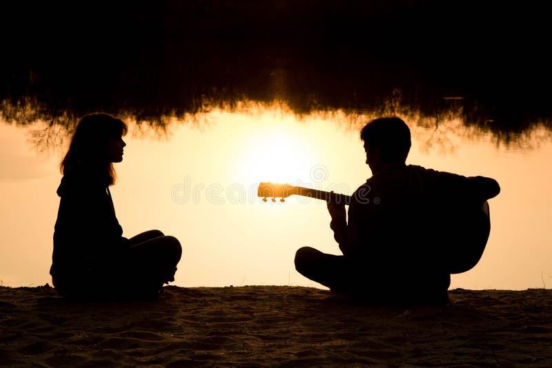 一个男孩和女孩的剪影海滩的与吉他 免版税库存照片
